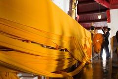 El monje y la gente tailandesa que hacen la manta de la tela de la ceremonia cubren chedi Imágenes de archivo libres de regalías
