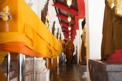 El monje y la gente tailandesa que hacen la manta de la tela de la ceremonia cubren chedi Foto de archivo libre de regalías
