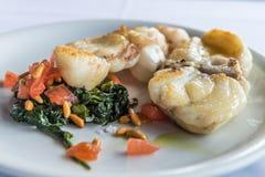El monkfish asado a la parrilla adornó espinaca con la nuez y los tomates de cedro foto de archivo libre de regalías