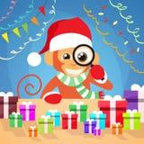 El mono de la Navidad elige la caja de regalo en Año Nuevo del escritorio Fotografía de archivo libre de regalías