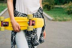 El monopatín plástico amarillo con verde rueda adentro las manos femeninas Foto de archivo