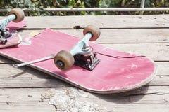 El monopatín roto viejo miente con una llave inglesa en una tabla de madera en el aire abierto imágenes de archivo libres de regalías