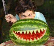 El monstruo de la demostración del muchacho del adolescente con los dientes cortados del tiburón riega el melong Imagen de archivo