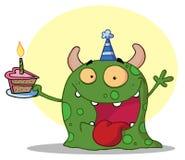 El monstruo verde feliz celebra cumpleaños con la torta Imagen de archivo libre de regalías