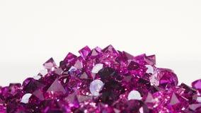 El montón de piedras violeta de la joya que vuelca blanco, coloca listo almacen de video