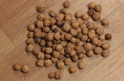 El montón grande de nueces dispersó en un piso Fotos de archivo