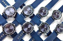 Es el reloj de mucho hombre con el dial y el azul azules las mentiras de una correa en un fondo blanco Imagen de archivo