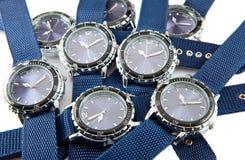El montón grande del reloj de un hombre con el dial y el azul azules una correa miente en un fondo blanco Imagen de archivo libre de regalías