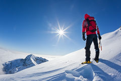 El montañés alcanza el top de una montaña nevosa en un winte soleado fotografía de archivo libre de regalías