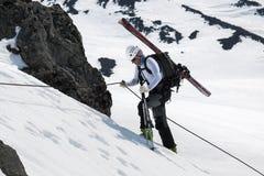 El montañés del esquí sube en la roca en una cuerda con los esquís atados con correa a una mochila Imágenes de archivo libres de regalías