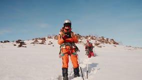 El montañés orgulloso se coloca en la colina de la nieve, pegando un polo de esquí en la nieve y mirando un mapa de la ruta en la almacen de video