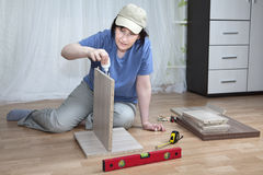 El montaje de los muebles, mujer lubrica la superficie del chipboa adhesivo imagen de archivo libre de regalías