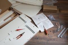 El montaje de los muebles parte y las herramientas para los muebles de la asamblea del uno mismo, en el piso Fotografía de archivo