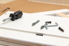El montaje de los muebles parte y las herramientas para los muebles de la asamblea del uno mismo, en el piso foto de archivo
