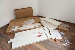 El montaje de los muebles parte y las herramientas para los muebles de la asamblea del uno mismo, en el piso Fotos de archivo