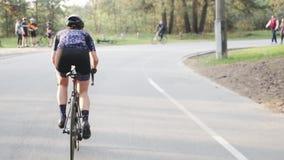 El montar atractivo joven de la mujer del ciclista ascendente fuera de la silla de montar Detrás siga el tiro Concepto de ciclo almacen de metraje de vídeo