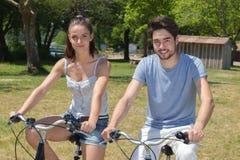 El montar a caballo adolescente de los pares del retrato al aire libre monta en bicicleta en naturaleza Imagen de archivo libre de regalías