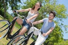 El montar a caballo adolescente de los pares del retrato al aire libre monta en bicicleta en naturaleza Imagenes de archivo