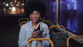 El montar a caballo afroamericano feliz de la mujer en el transporte público, cierra el libro después de leer y de mirar fuera de metrajes