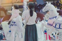 El montar a caballo asiático adorable de la muchacha del niño en un feliz va ronda carous fotografía de archivo