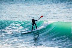 El montar a caballo de la persona que practica surf encendido se levanta el tablero de paleta en onda grande Invierno que practic foto de archivo libre de regalías