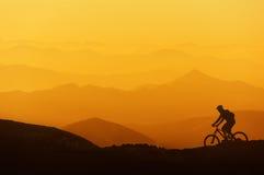 El montar a caballo del motorista en la montaña siluetea el fondo Fotos de archivo