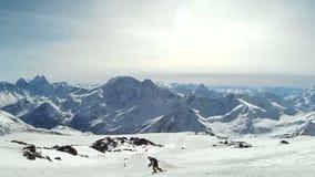 El montar a caballo del Snowboarder en las montañas en el esquí se inclina metrajes