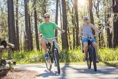 El montar a caballo feliz de los pares bikes junto en una trayectoria de la bici en el bosque imagenes de archivo