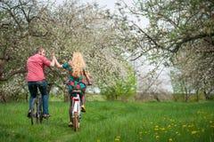 El montar a caballo joven cariñoso de los pares monta en bicicleta en el jardín de la primavera Imagenes de archivo