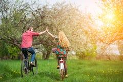 El montar a caballo joven cariñoso de los pares monta en bicicleta en el jardín de la primavera fotos de archivo