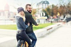 El montar a caballo joven de los pares bikes y divirtiéndose en la ciudad Imagen de archivo libre de regalías