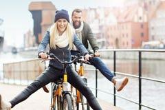 El montar a caballo joven de los pares bikes y divirtiéndose en la ciudad Imágenes de archivo libres de regalías