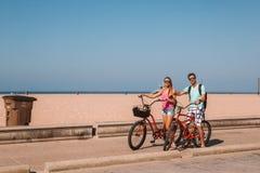 El montar a caballo joven de los pares monta en bicicleta abajo de la playa de Venecia en Los Ángeles Foto de archivo