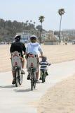 El montar de la familia bicis foto de archivo