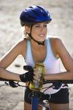 El montar en bicicleta de la mujer joven. Foto de archivo