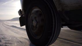 El montar en el hielo del lago y de mucha nieve La rueda posterior del coche almacen de metraje de vídeo