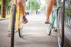 El montar y el viaje de las mujeres por la ciudad del vintage monta en bicicleta Fotografía de archivo libre de regalías