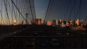 El montar y los peatones de los coches caminan sobre el puente de Brooklyn en la puesta del sol almacen de metraje de vídeo