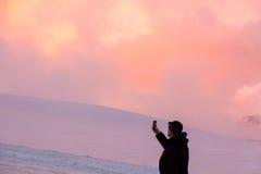 El monte Elbrus, Rusia, hombre toma una imagen en el teléfono en las montañas durante puesta del sol Foto de archivo