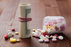 El montón de las píldoras farmacéuticas de la droga y de la medicina dispersó de las botellas con el dinero del efectivo del dóla Foto de archivo libre de regalías