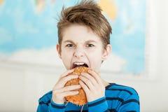El morder vegetariano joven en una hamburguesa de la zanahoria Fotos de archivo libres de regalías