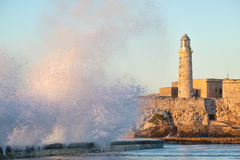 El morro fortress and lighthouse of Havana at sunset. With huge sea waves crashing on the Malecon seawall Royalty Free Stock Photo