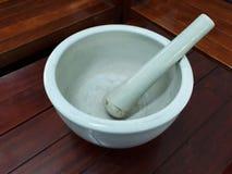 El mortero de cerámica blanco, puso una tabla de madera fotos de archivo