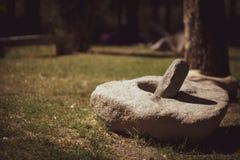 El mortero de piedra es una herramienta para machacar las hierbas, las flores, las especias, las hojas, las raíces y otras comida imagenes de archivo