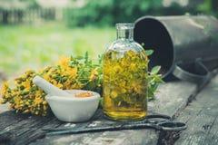 El mosto de St Johns florece, aceite o la botella transparente de la infusión, mortero en la tabla de madera al aire libre Imagen de archivo libre de regalías