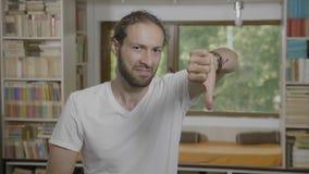 El mostrar de evaluación del hombre adolescente manosea con los dedos encima de los pulgares abajo que dan diversa reacción - almacen de video