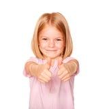El mostrar feliz de la niña los pulgares sube la muestra Imagen de archivo libre de regalías