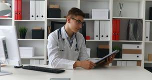 El mostrar joven del doctor de papel y sonrisa en la cámara almacen de metraje de vídeo