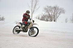 El motocrós en nieve, el conductor maneja el brazo de la motocicleta una en nieve Fotografía de archivo