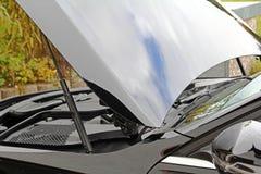 El motor de un coche negro con el capo abierto fotos de archivo
